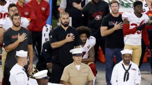 Quarterback Colin Kapernick kneels during the national anthem next to former Green Beret Nate Boyer, (CAP photo)
