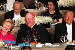 Cardinal Timothy Dolan seated between Hillary Clinton and Donald Trump.